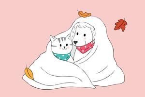 Gatto e cane di autunno in coperta