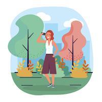 Donna con lo smartphone che cammina nel parco vettore