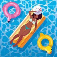 donna afro abbronzatura in galleggiante sulla piscina