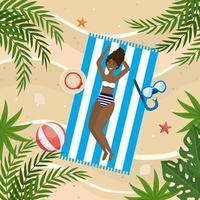 donna che prende il sole con maschere da snorkeling e cappello nell'asciugamano