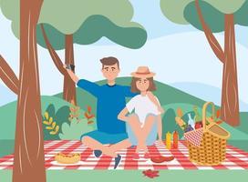 uomo e donna nella tovaglia con cesto e cibo