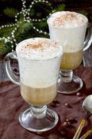 cappuccino met een versierde kerstboom op een houten tafel
