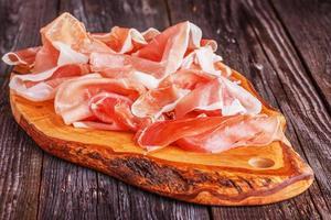 Prosciutto geserveerd op een snijplank voor olijven
