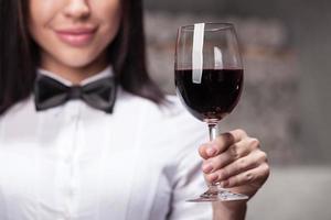 vrolijke vrouwelijke slijterij assistent met wijnglas