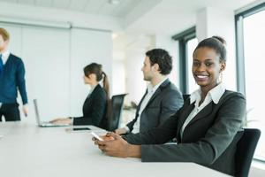 jonge mensen uit het bedrijfsleven zitten aan een vergadertafel en leren