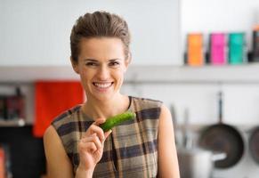 glimlachende vrouw die verse komkommer houdt