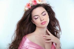 zacht mooi meisje met delicate bloemen in lang golvend haar
